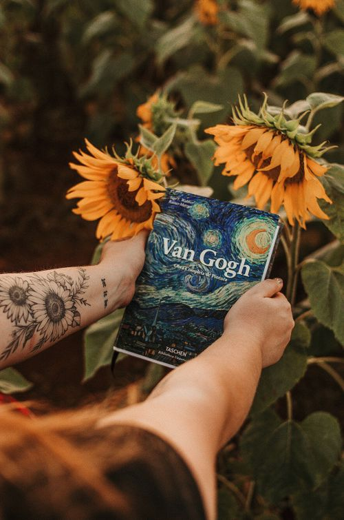 Canva Person Holding Van Gogh Book Beside Sunflowers